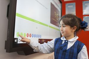 student playing with digital TV monitor at school