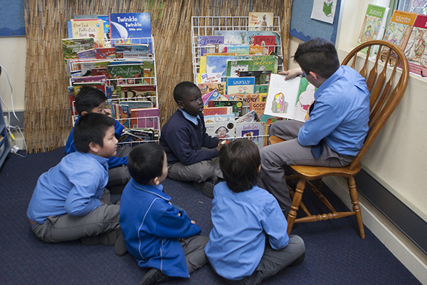 students in a circle reading a book